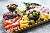Italian appetizers or antipasto set mixed delicatessen of cheese and meat snacks. Gray background. Top view