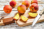 Fresh Peaches, organic fruit on the chopping Board. White wooden background. Top view