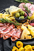 Antipasto platter with ham, prosciutto, salami, blue cheese, mozzarella and olives. Black background. Top view