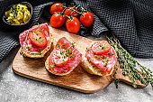 Canapes with salami salchichon, cherry tomatoes and micro greens on a baguette. gray background. top view