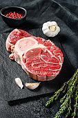 Osso Buco meat. Raw cross cut veal shank and seasonings for cooking Osso Buco. Black background. Top view