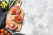 Canapes with salami salchichon, cherry tomatoes and micro greens on a baguette. gray background. top view. Copy space