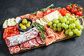 Italian antipasto, wooden cutting board with prosciutto, ham, parma,  goat  and Camembert cheese, olives, grapes. antipasti. Black background. Top view