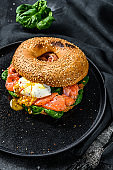 Homemade Bagel sandwich with salmon, cream cheese, spinach and egg. Black background. Top view