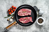 Raw pork steak in a frying pan. Marbled farm meat. Gray background. Top view. Space for text.