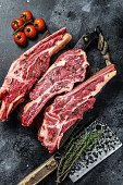 Assortment of raw cuts beef meat steaks on the bone. Black background. Top view