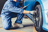 Asian car mechanic technician holding clipboard and checking to maintenance vehicle by customer claim order in auto repair shop garage. Wheel tire repair service. People occupation and business job