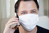 The man with the mask on his face is talking on the phone. Coronavirus and quarantine concept.