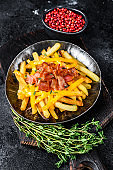 Delicious golden French fries with melted cheddar cheese and bacon. Black background. Top view