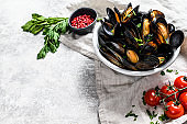 Mussels with herbs and sauce in bowl.  Gray background. Top view. Space for text