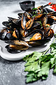 Raw mussels in shells on a chopping Board. The concept of cooking seafood in tomato sauce with parsley. Gray background. Top view