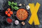 Italian food ingredients for Spaghetti Bolognese. Raw pasta, Basil, ground beef, tomatoes. Black background. Top view