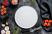 White empty plate in center of Fresh raw greens, vegetables. Healthy, clean eating, vegan, dieting food concept. Black background. Top view. Copy space