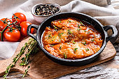 Baked halibut fish in a pan with tomato sauce. White wooden background. Top view
