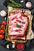 Fresh raw pork ribs with rosemary, pepper and garlic. Farm organic meat. Black background. Top view