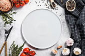 White empty plate in center of Fresh raw greens, vegetables. Healthy, clean eating, vegan, dieting food concept. White background. Top view. Copy space