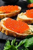 Red caviar in bowl and Sandwiches on stone board. Black background. Top view