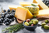 Cheese plate served with grapes, crackers, olives and nuts. Assorted delicious snacks. Gray background. Top view
