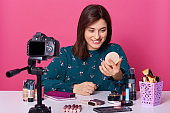Useful beauty blog. Nice attractive brunette woman giving advice about cosmetics while having her beauty blog, holding handy mirror in hands, female posing isolated over pink studio background.