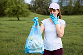 Shocked lady covering her mouth while looking at blue garbage bag full of litter collects in meadow, woman worries about cleanliness environment and pollution problems.