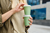 Green paper cup with coffee in woman hand. Time for drink coffee in city. Coffee to go. Enjoy moment, take a break. Disposable paper cup closeup. Delicious hot beverage. Blank space for text, mockup