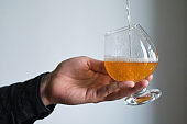 A glass of beer in the hands of a man. Tasting brewed craft beer. Lager beer with beautiful foam. Cold refreshment beverage. Alcohol drink from pub. Relaxation and enjoyment on beer degustation