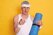 Horizontal shot of mature man pointing directly at camera with his forefinger, holding blue yoga mat in hands, doing physical exercises every day, calls on to go in for sport. Lifestyle concept.