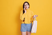 Young woman with cotton shopping bag talking on mobile phone while looking up, lady holding eco bag in hands, wearing yellow sweater and jeans short.