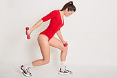 Picture of beautiful sporty attractive woman being focused on result, developing her body, doing strength exercises, posing isolated over white background in studio. People and health concept.