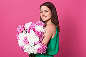 Horizontal shot of beautiful brunette girl holding white and rose peonies in hands, attractive woman with charming smile, female emraces flowers, dressed green sundress, posing against pink background