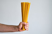 Uncooked spaghetti bunch in the hands of a man. Traditional italian pasta, healthy organic food. Raw ingredient for eating. Cooking homemade delicious cuisine for family. Durum wheat spaghetti closeup
