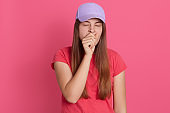 Closeup portrait of tired yawning woman covering her mouth with fist, looks exhausted, wearing t shirt and baseball cap, wants sleep, posing isolated over pink background.