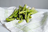 Green asparagus on the white cloth. Bundle of ripe fresh asparagus. Healthy organic food. Cooking in home. Natural vitamins, raw ingredient for eating. Handpicked bio asparagus