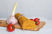 Uncooked spaghetti bundle, tomatoes and garlic on kitchen table. Traditional italian pasta, organic food. Raw ingredient for eating. Cooking homemade delicious cuisine. Durum wheat spaghetti closeup