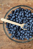 Blueberries on a spoon in a bowl. Natural organic berries. Fresh beautiful blueberry close up. Delicious summer wild berry. Berries for dessert. Healthy lifestyle, vegetarian sweet snack