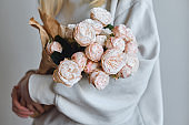 White-pink roses in the hands of a happy woman. Rose petal close-up. Beautiful holiday spring bouquet. Florist girl with blossom flower. Fresh floral bunch. Romantic surprise from a loved one