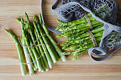 Green asparagus on cutting board. Bundle of ripe fresh asparagus. Healthy organic food. Cooking in home. Natural vitamins, raw ingredient for eating. Handpicked bio asparagus