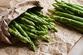 Green asparagus on kraft paper. Bundle of ripe fresh asparagus. Healthy organic food. Cooking in home. Natural vitamins, raw ingredient for eating. Handpicked bio asparagus