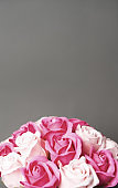 Buds of pink and white roses on a grey background.