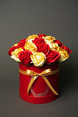 Flowers in bloom: A bouquet of red and golden roses in a red round box on a gray background.