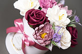 Flowers in bloom: multi-colored red and pink buds in a white round box on a grey background.