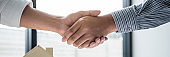 Real estate agent and customers shaking hands together celebrating finished contract after signing about home insurance and investment loan, handshake and successful deal