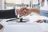 Handshake after good cooperation, Businesswoman Shaking hands with Professional male lawyer after discussing good deal of contract in courtroom, Concepts of law, Judge gavel with scales of justice