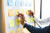 Two creative Business people meeting and planning use post it notes sticky note on board to share idea, Analysis data charts and graph with teamwork strategy brainstorming