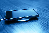 Mobile smart phone charging wirelessly by sharing battery via device in classic blue color.