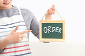 Portrait of waitress showing chalkboard with order sign on white