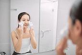 Skincare woman washing face in shower foaming face wash soap scrub on skin. Enjoying relaxing time