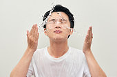 Handsome young man is washing his face, splashes of water around, white background