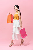 Full length portrait of a beautiful young woman posing with shopping bags, isolated against pink background