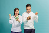 Surprised young couple stand isolated on blue background hold smartphones happy win online lottery,